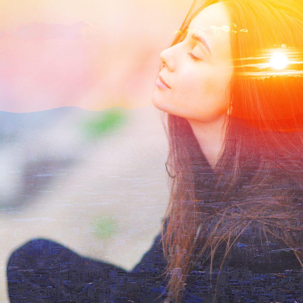 giovane donna in meditazione con sole