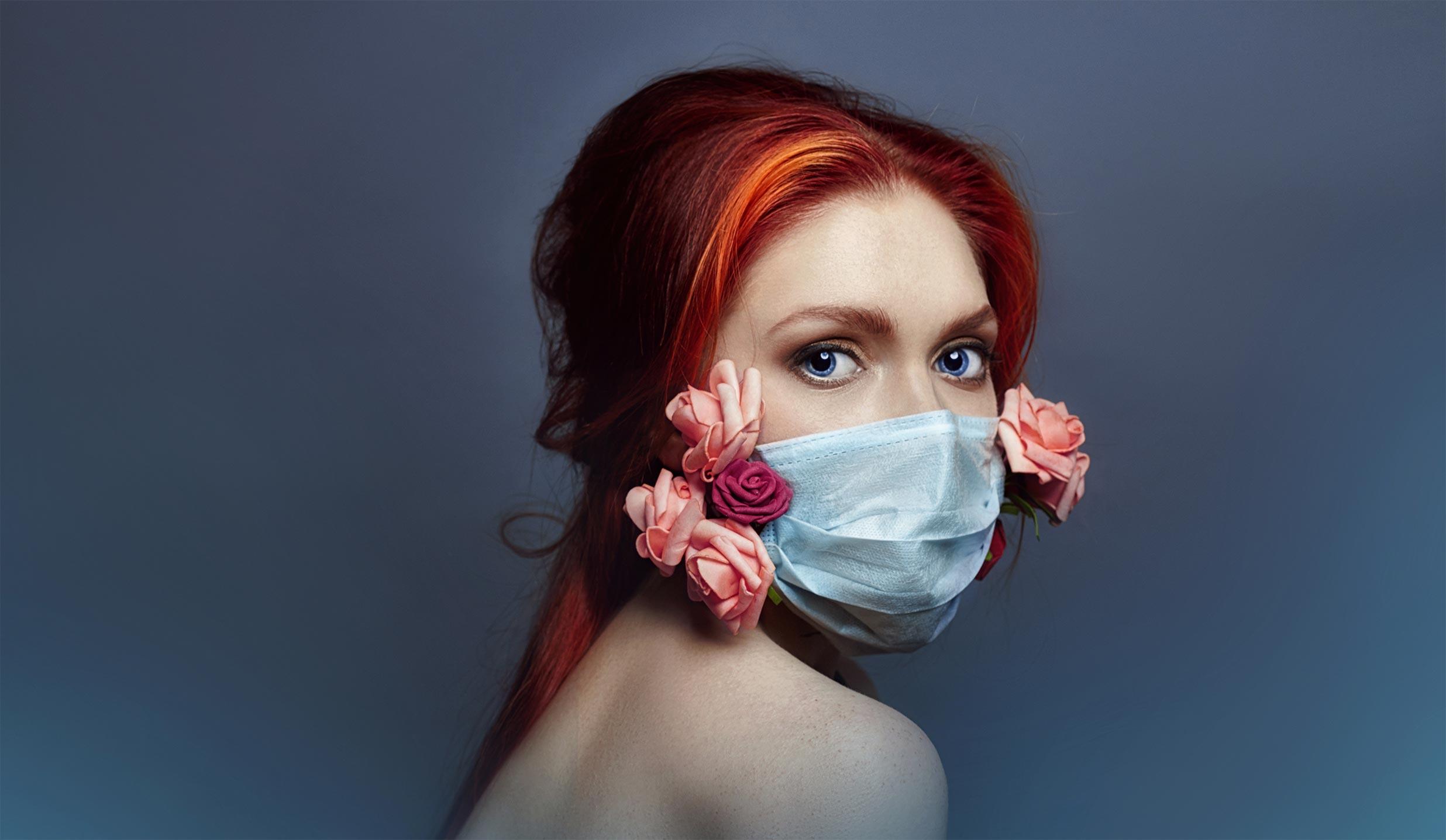 Donna con i capelli rossi e una mascherina ornata di fiori per difendersi da coronavirus