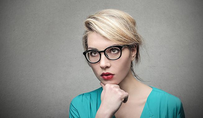 donna bionda con occhiali e pensierosa