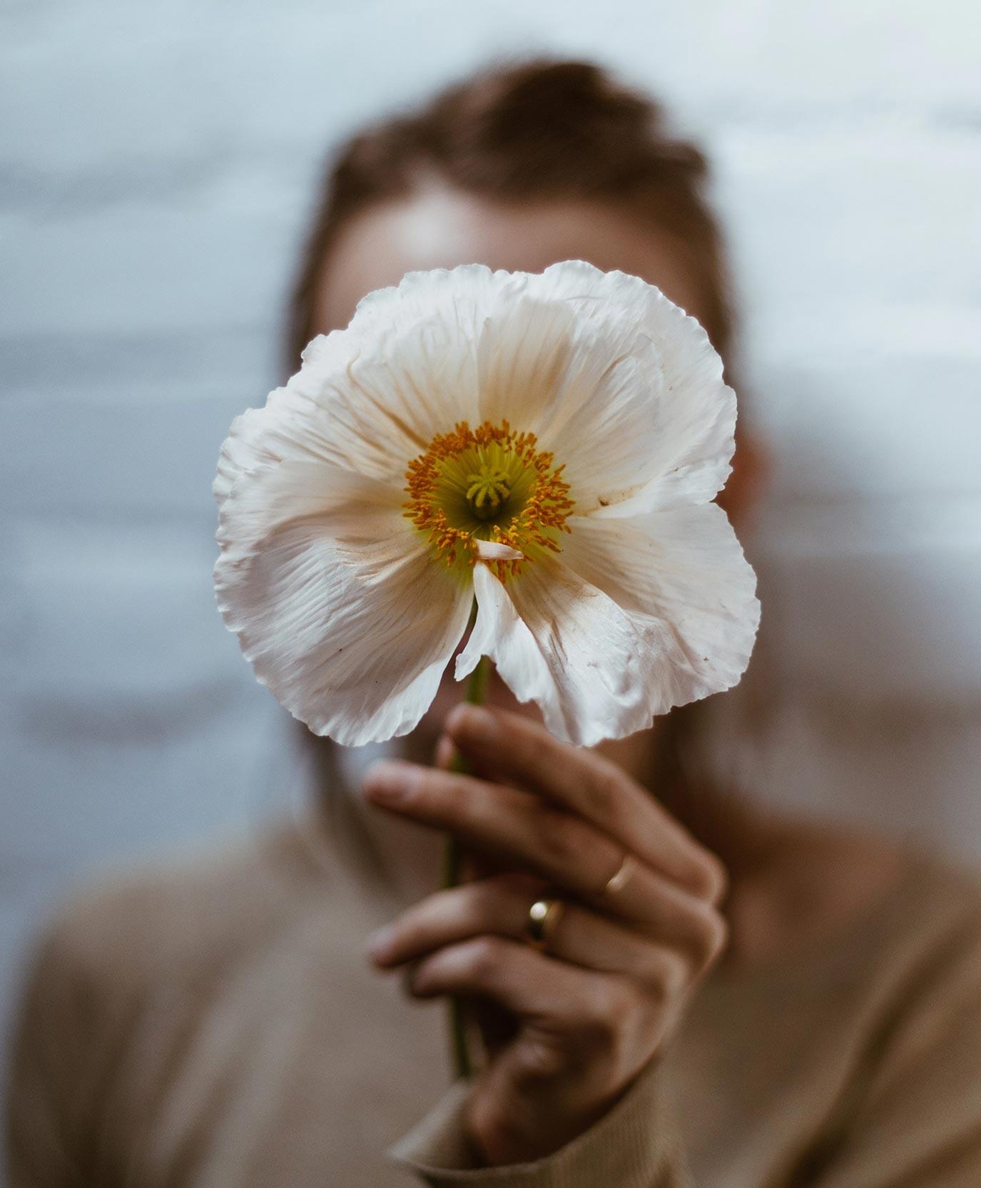 donna con fiore in mano davanti al viso