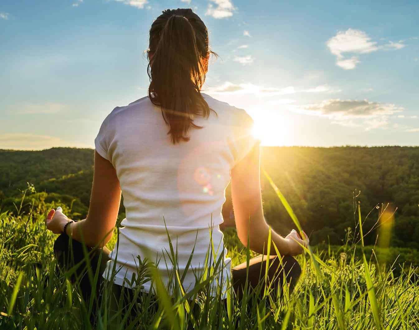 donna in meditazione di fronte al sole