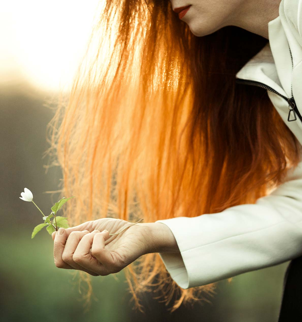 donna con capelli rossi raccoglie fiore