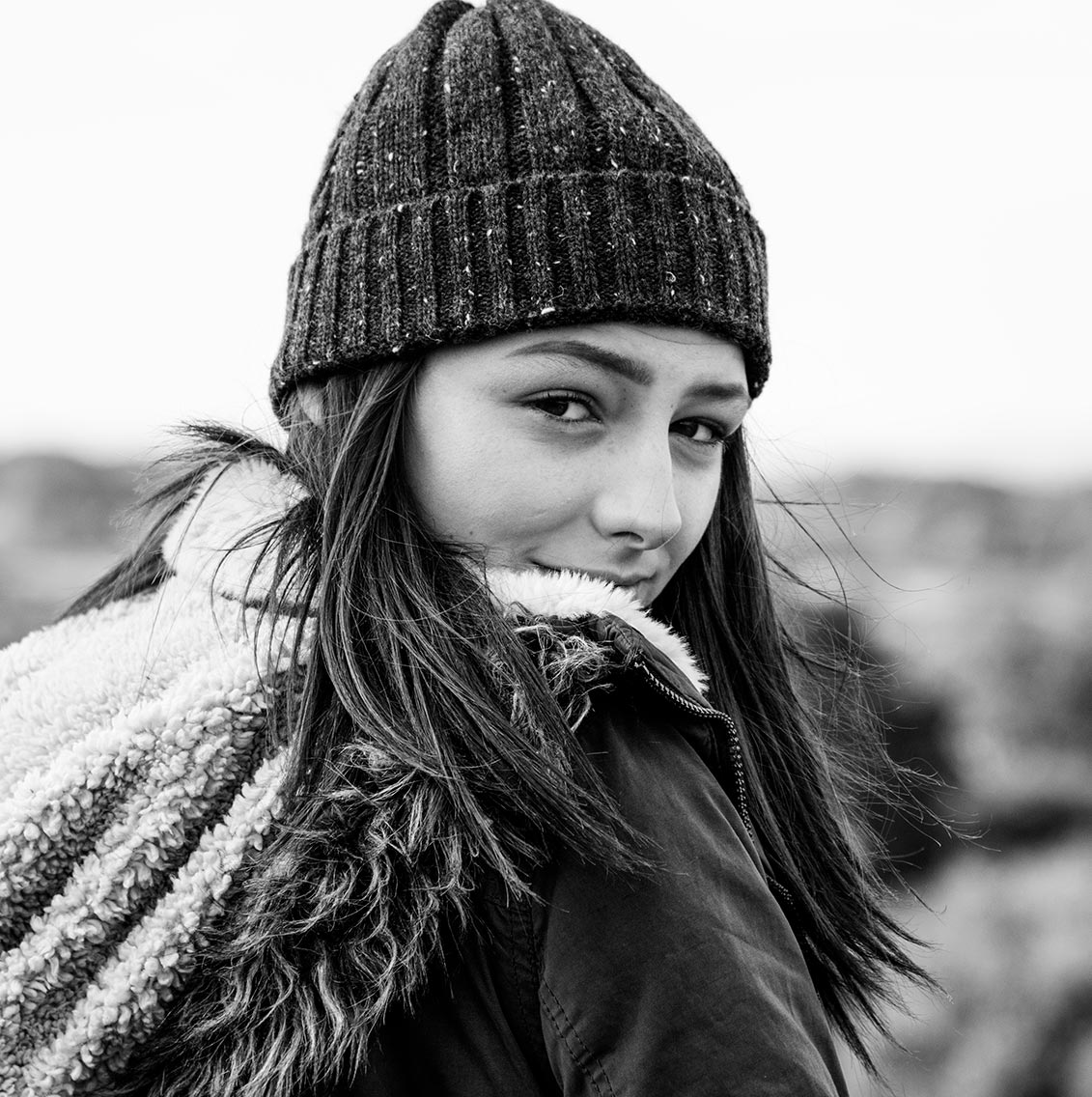 ragazza mora con berretta e sguardo rivolto indietro per scoprire il coraggio