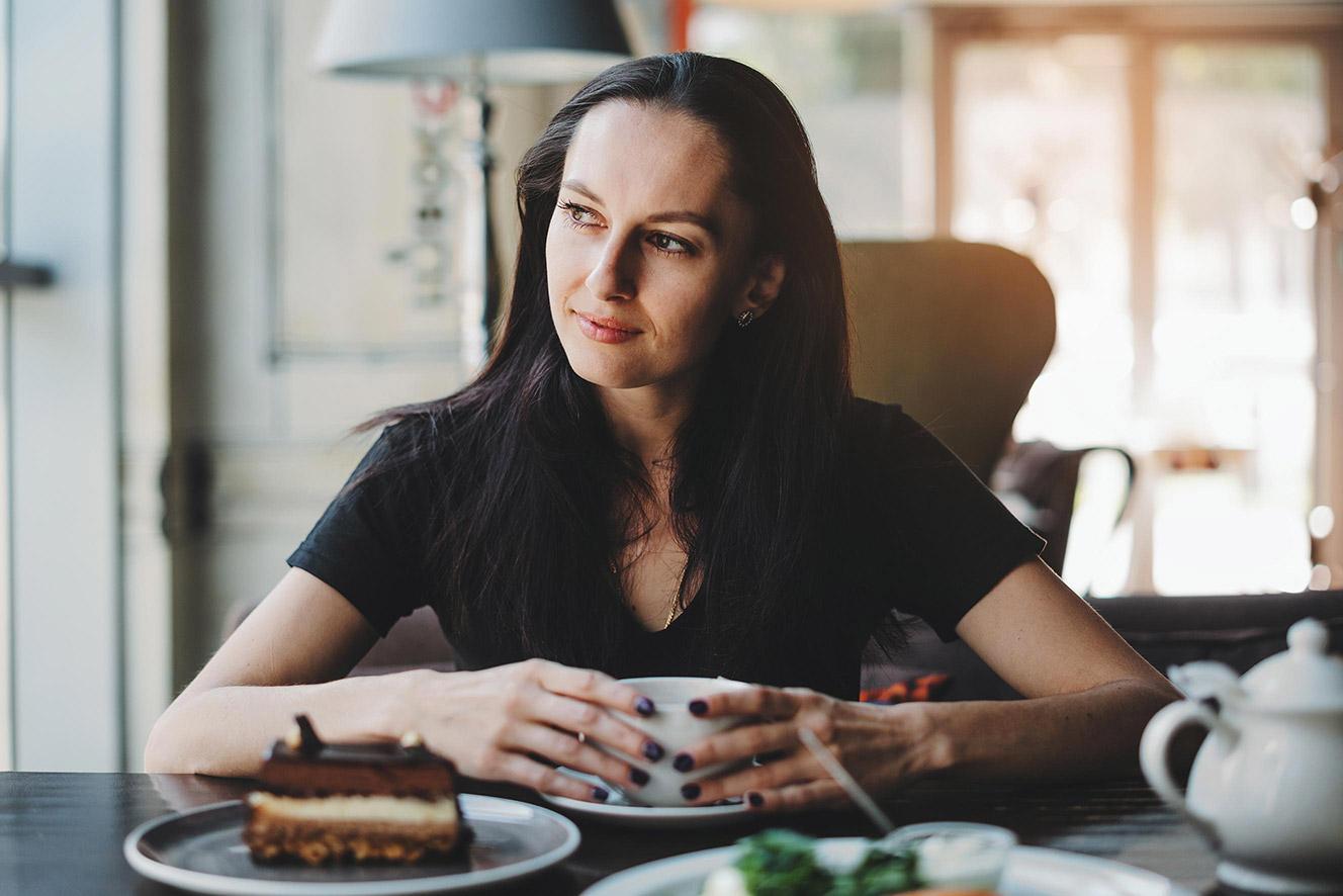 donna mora con tazza caffè e sguardo lontano