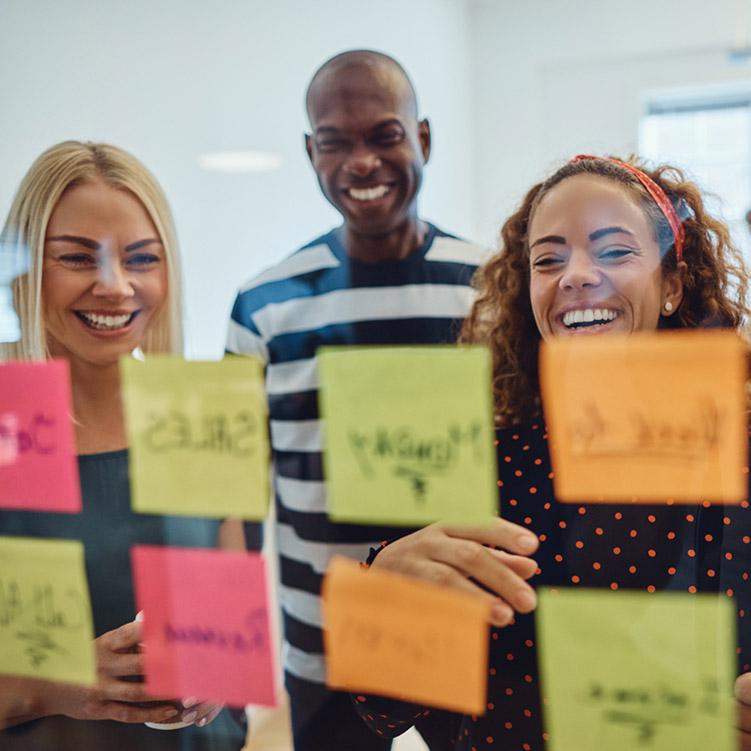 giovani colleghi sorridenti al lavoro con post.it