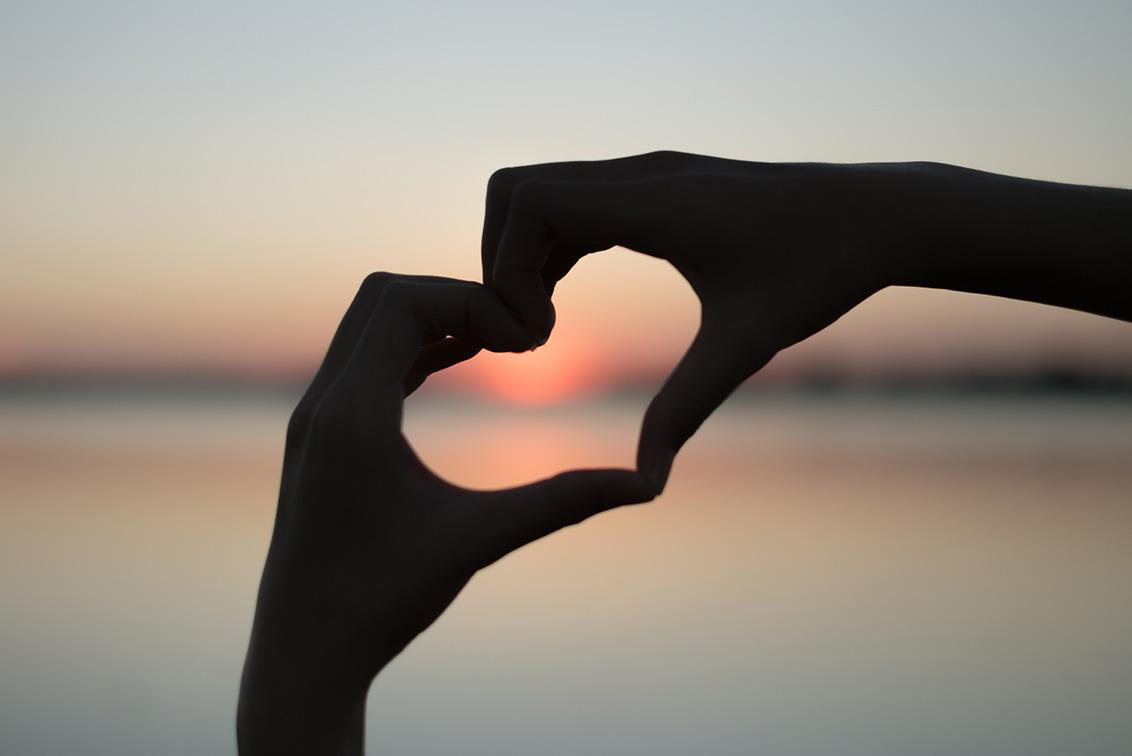 mani che formano cuore al tramonto