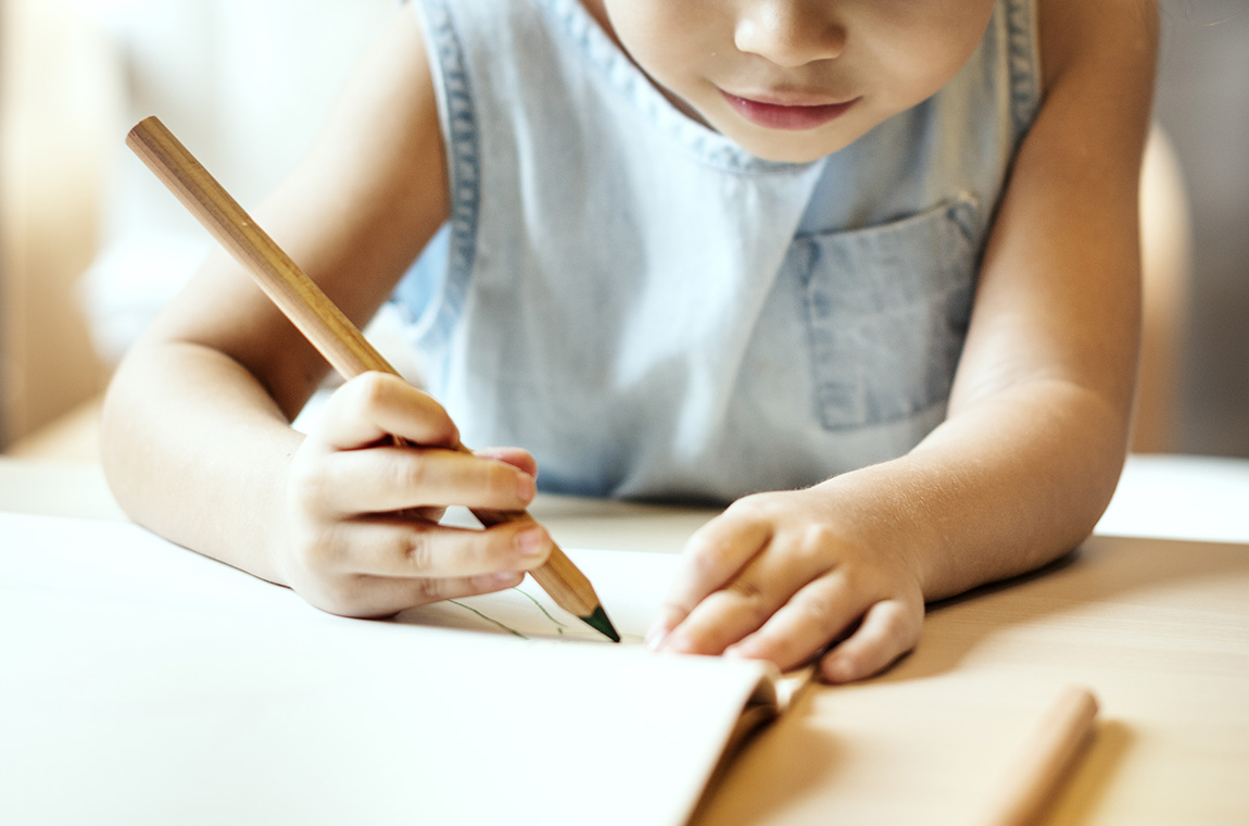 bambina al tavolo che scrive