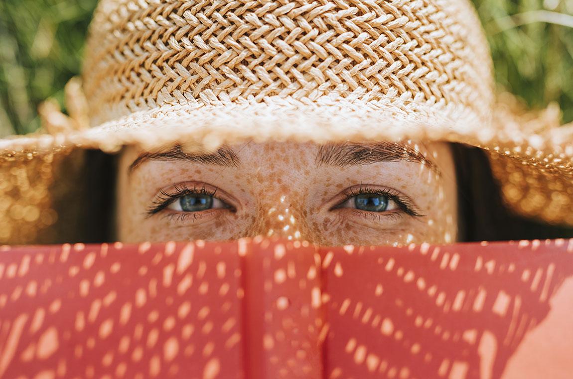 donna con lentiggini e cappello di paglia