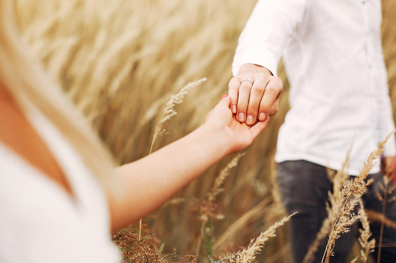 mani congiunte in un campo di grano